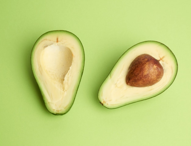 Half ripe green avocado with a brown pit on a green background
