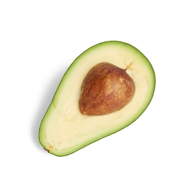 Half ripe green avocado with a brown pit isolated on a white background, healthy and tasty fruit, top view