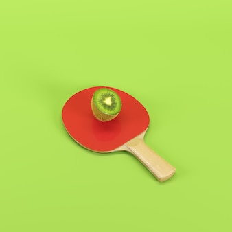 Half of ripe kiwi fruit on ping pong paddle isolated on green background