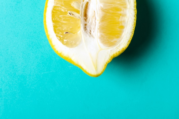 Half of ripe lemon on blue
