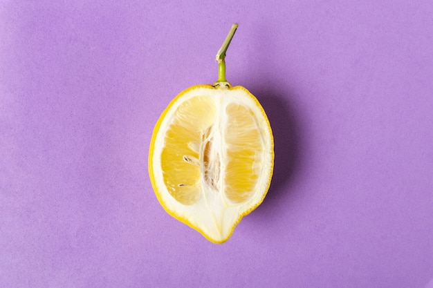 Half of ripe lemon on purple