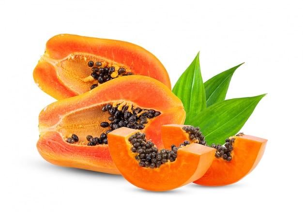 Половина спелой папайи с листьями на белой стене.