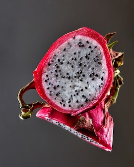 Half of the ripe pitahaya or dragon fruit is reflected