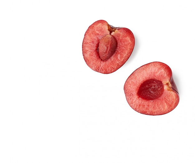 Half ripe red sweet cherry with pit isolated on white background, macro, top view