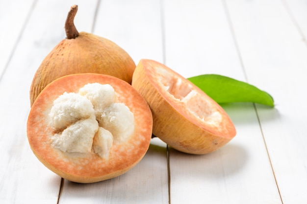 Половина сантола на деревянном фоне, у сантола кисловатый вкус, а середина сантола более сладкая. это очень известный фрукт провинции лопбури. таиланд