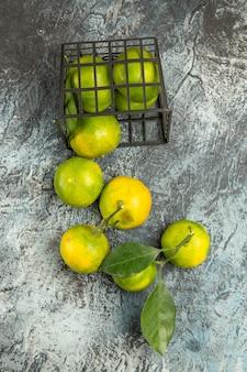 Mezza ripresa di un cesto con mandarini verdi freschi tagliati a metà e mandarino sbucciato su sfondo grigio