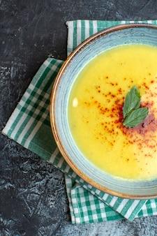 Mezzo colpo di una pentola blu con una gustosa zuppa servita con menta su un asciugamano verde spogliato su sfondo blu
