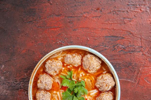 Mezzo colpo di zuppa di pollo con noodles in una ciotola marrone su sfondo scuro