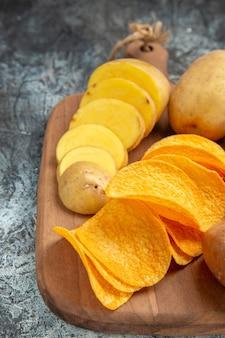 Mezzo colpo di patatine croccanti e patate crude sul tagliere di legno sul metraggio tavolo grigio