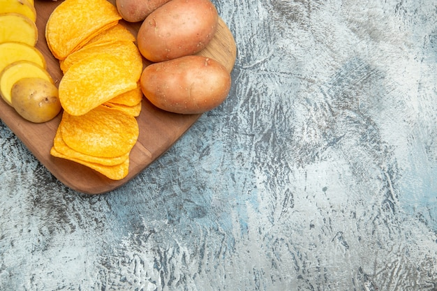 Half shot of crispy chips and uncooked potatoes on wooden cutting board on gray table