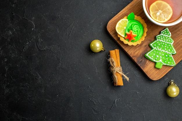 Mezzo colpo di una tazza di accessori per il tè nero cono di conifere e lime alla cannella su sfondo nero
