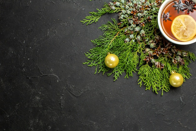 Half shot of a cup of black tea xsmas accessories and cinnamon limes on black background