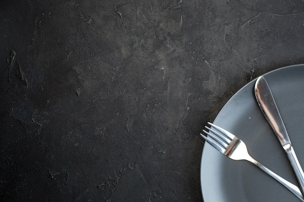 Half shot of cutlery set on a black plate on the left side on dark color background with free space
