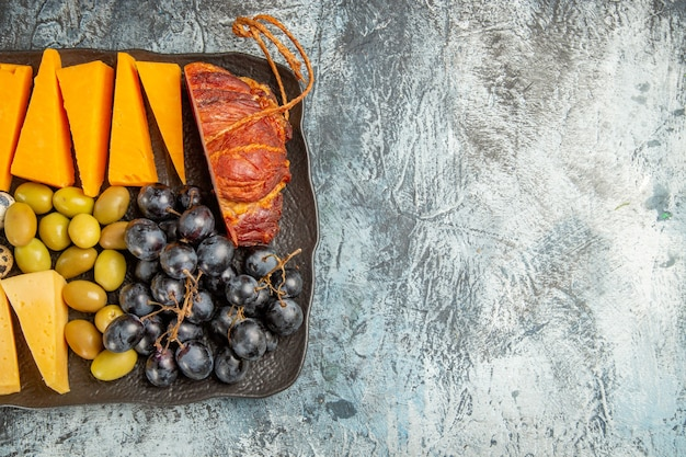 Half shot of delicious best snack for wine served on brown tray on the right side on gray background