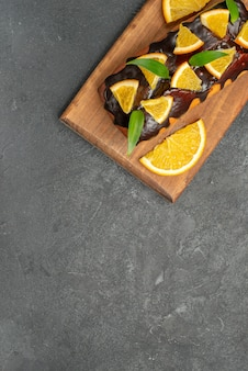 Half shot of delicious cakes decorated with lemon and chocolate on cutting board on black table