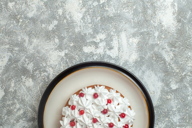 Half shot of delicious creamy cake decorated with fruits on ice background