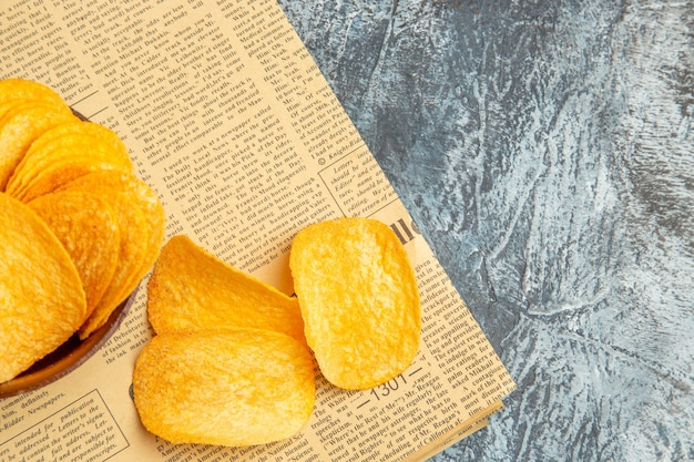 Half shot of delicious homemade chips on newspaper on gray table