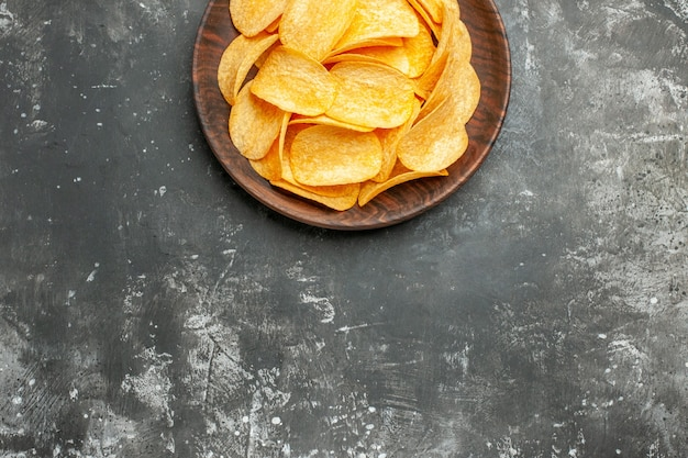 Half shot of delicious homemade potato chips on a brown plate on gray table