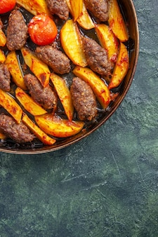 Half shot of delicious meat cutlets baked with potatoes and tomatoes on green and black mix color background in vertical view
