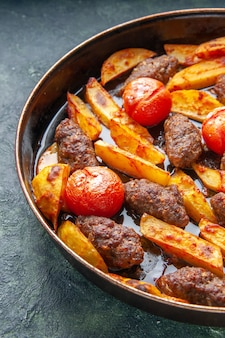 Half shot of delicious meat cutlets baked with potatoes and tomatoes on green and black mix color background