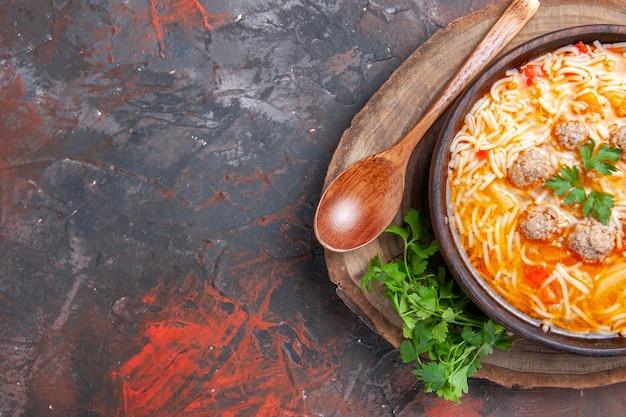 Mezzo colpo di deliziosa zuppa di noodle con pollo su tagliere di legno cucchiaio di verdure su sfondo scuro