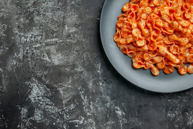 Half shot of delicious pasta meal on a black plate for dinner on dark table