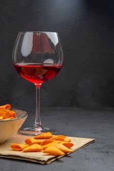 Mezzo colpo di deliziose patatine dentro e fuori la ciotola e vino rosso in un bicchiere su un vecchio giornale