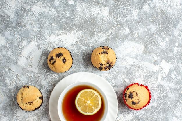 Mezzo colpo di deliziosi piccoli cupcakes con cioccolato intorno a una tazza di tè nero sulla superficie del ghiaccio