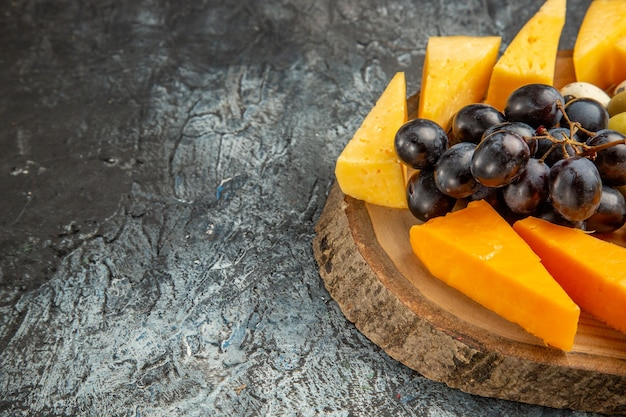Mezzo colpo di delizioso spuntino con frutta e cibi su un vassoio marrone sul lato sinistro su sfondo di ghiaccio