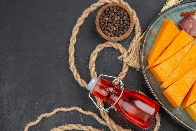 Mezza foto di deliziosi snack bottiglie cadute peperoni su asciugamano e corda su sfondo nero
