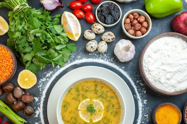 Mezzo colpo di deliziosa zuppa servita con limone e verde in una ciotola bianca e farina di pomodoro olio bottiglia farina verde fasci uova al buio