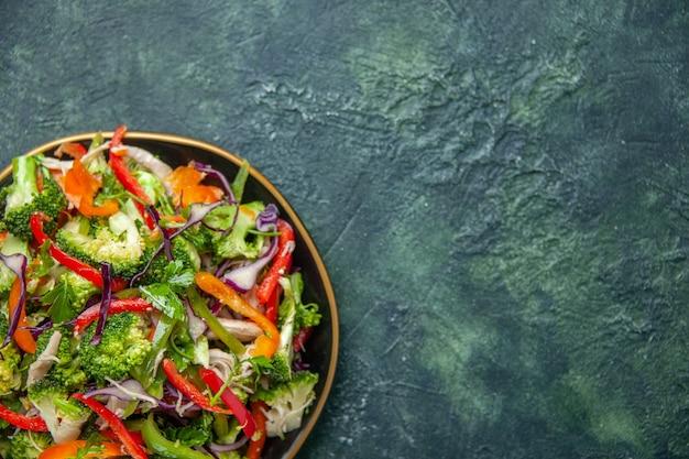 Mezzo colpo di deliziosa insalata vegana in un piatto con varie verdure fresche sul lato destro su sfondo scuro