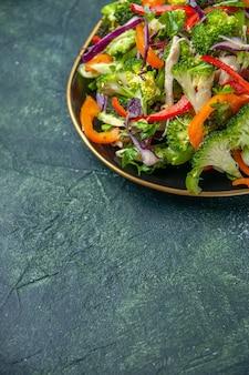 Mezzo colpo di deliziosa insalata vegana in un piatto con varie verdure su sfondo scuro