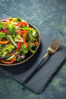 Mezzo colpo di deliziosa insalata vegana con ingredienti freschi in un piatto e forchetta su tagliere nero su sfondo blu
