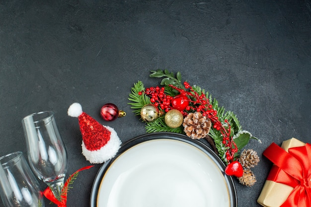 Metà colpo di piatto di cena albero di natale rami di abete conifera cono confezione regalo cappello di babbo natale calici di vetro caduti su sfondo nero