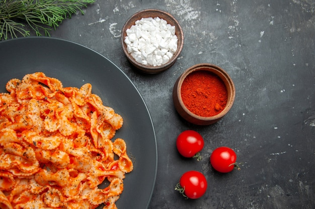 Half shot of easy pasta meal for dinner on a black plate and different spices and tomatoes on a dark background