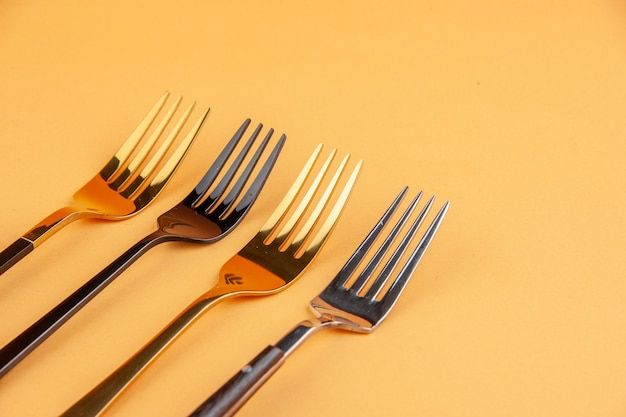 Mezzo colpo di eleganti forcelle in acciaio inox lucido su sfondo dorato isolato con spazio libero