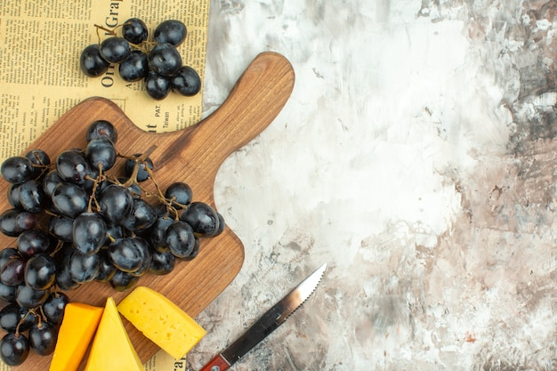 Half shot of fresh delicious black grape bunch and various kinds of cheese on wooden cutting board