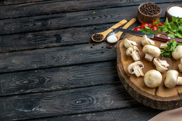 Half shot of fresh mushrooms and knife tomatoes spices on wooden board towel on black background