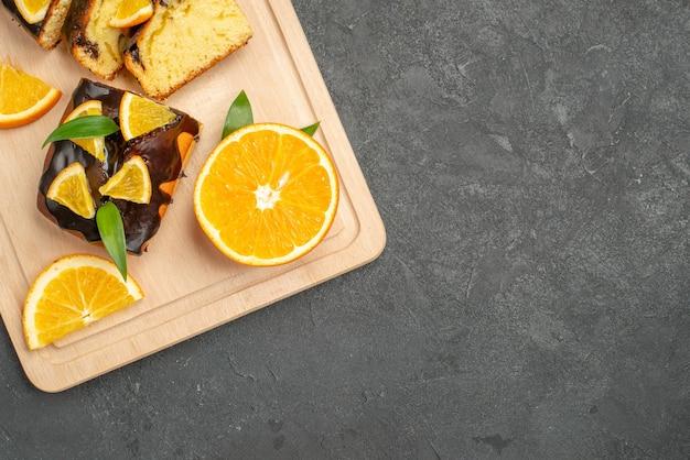 Mezzo colpo di fette d'arancia fresche e fette di torta tritate sul tavolo scuro