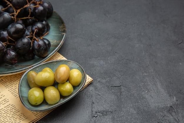 Mezzo colpo di olive verdi organiche fresche e fasci di uva nera su un vecchio giornale su sfondo scuro