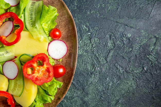 Half shot of fresh peeled cut potatoes with red pepper radishes green tomatoes in a brown plate on the right side on green black mix colors surface