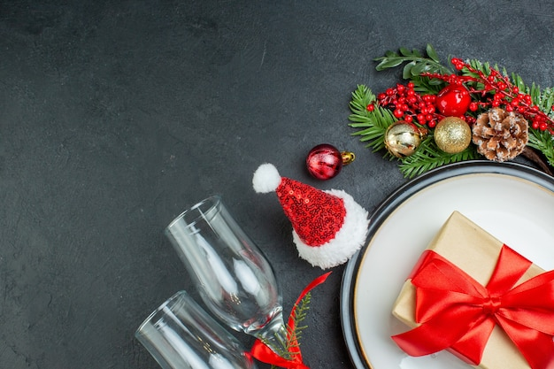Mezzo colpo di confezione regalo sul piatto di cena albero di natale rami di abete cono di conifere cappello di babbo natale calici di vetro caduti su sfondo nero