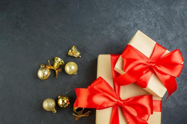 Metà colpo di confezione regalo con nastro rosso e accessori di decorazione su sfondo nero