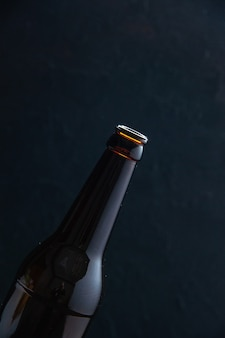 Half shot of glass bottle on black background with free space in vertical view Premium Photo