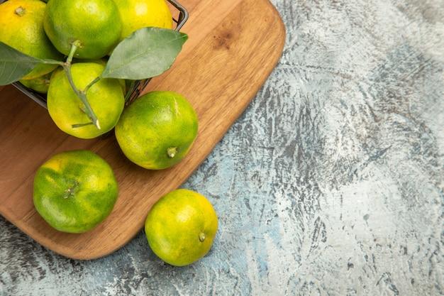 Mezzo colpo di mandarini verdi con foglie all'interno e all'esterno di un cesto su tagliere di legno su tavolo grigio