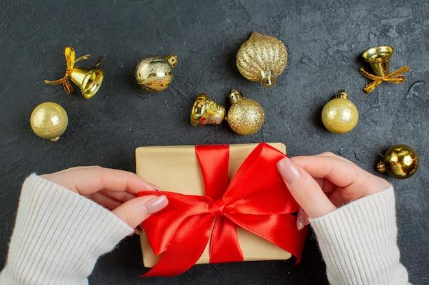 Mezzo colpo di mano che tiene una delle scatole regalo con nastro rosso e accessori di decorazione su sfondo scuro