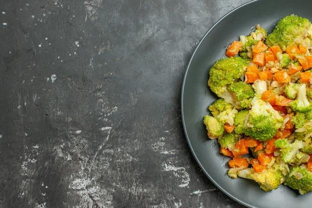 Mezzo colpo di pasto sano con broccoli e carote su un piatto nero sul tavolo grigio