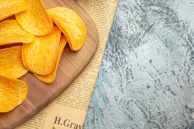 Half shot of homemade delicious potato chips on wooden cutting board on newspaper