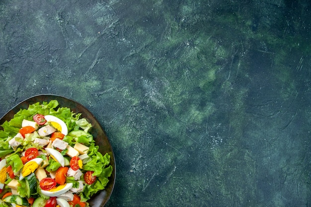 Half shot of homemade delicious salad in a black plate on the right side on green black mix colors background with free space